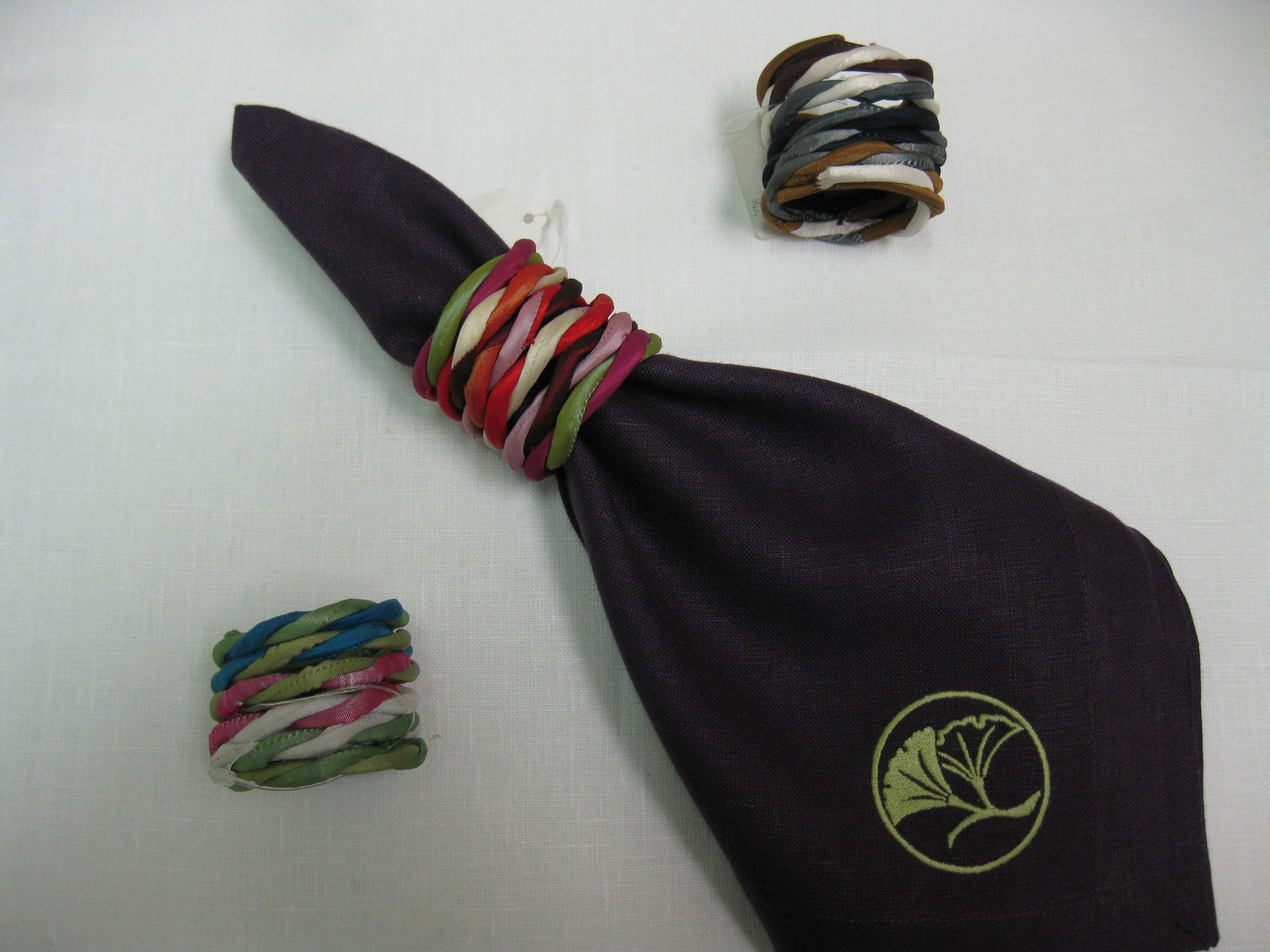 Napkin Rings From Left to Right:  Bright Multi Blue and Green, Bright Multi Reds and Natural Multi Napkin Plum with Embroidered Kiwi Ginko