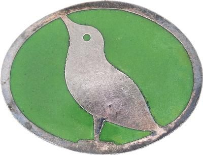 Kolo Moser, A brooch featuring a bird, designed in 1904, manufactured by the Wiener Werkstätte, silver plated and green enamelled metal, oval form, in Wiener Werkstätte cardboard box, marked on the reverse with three-line Wiener Werkstätte word mark, 3 x 2.2 cm, (B).