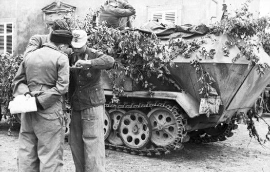 German Offiziers of the 21. Panzer-Division consult a map on the side of an Sd.Kfz. 251A