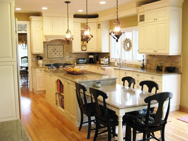 This french country classic kitchen features off white for Kitchens with islands in the middle
