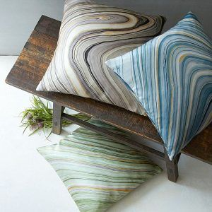 Earthy Tones Marble Pattern Throw Pillows Design Near Rustic WOod Bench Among Unstand Glass Vase Below It