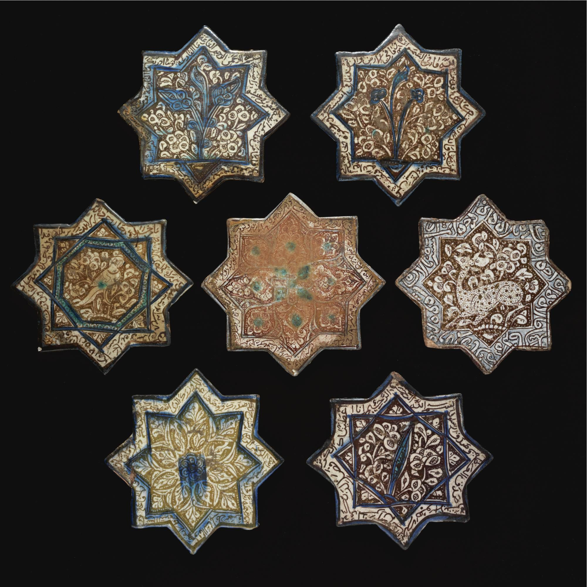 SEVEN PERSIAN LUSTER-PAINTED STAR TILES, KASHAN, SELJUK AND ILKHANID, 13TH CENTURY A.D. reserved in white with cobalt blue or turquoise detail, and painted respectively with a couchant deer, a bird, a rosette of radiating petals with blue splash in the center, a plant with tri-lobed flowers, a plant with fleur-de-lys, a tree or leaf, and an intricate radiating arabesque, all of the tiles with inscriptions in the borders.