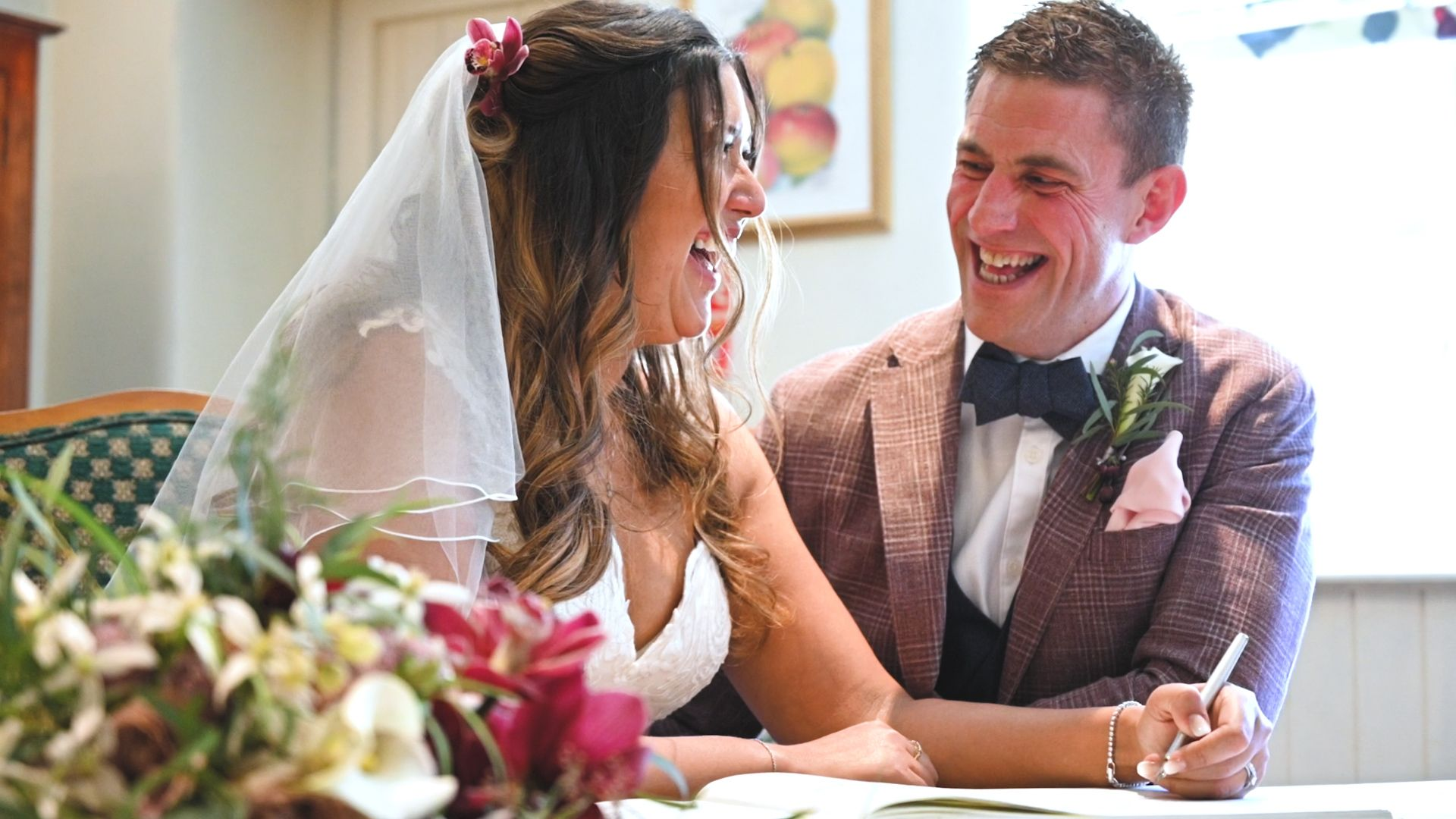 Bride and groom laughing as they sign the registar