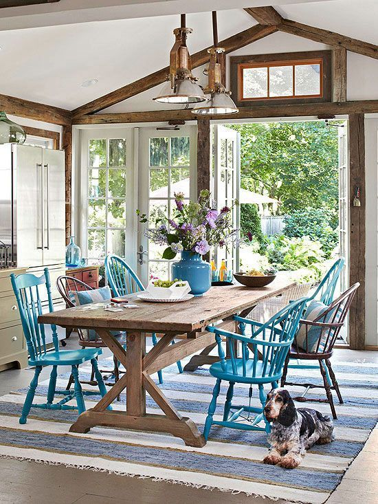 Coastal dining space with bright colored chairs, a trestle table and cute pup!