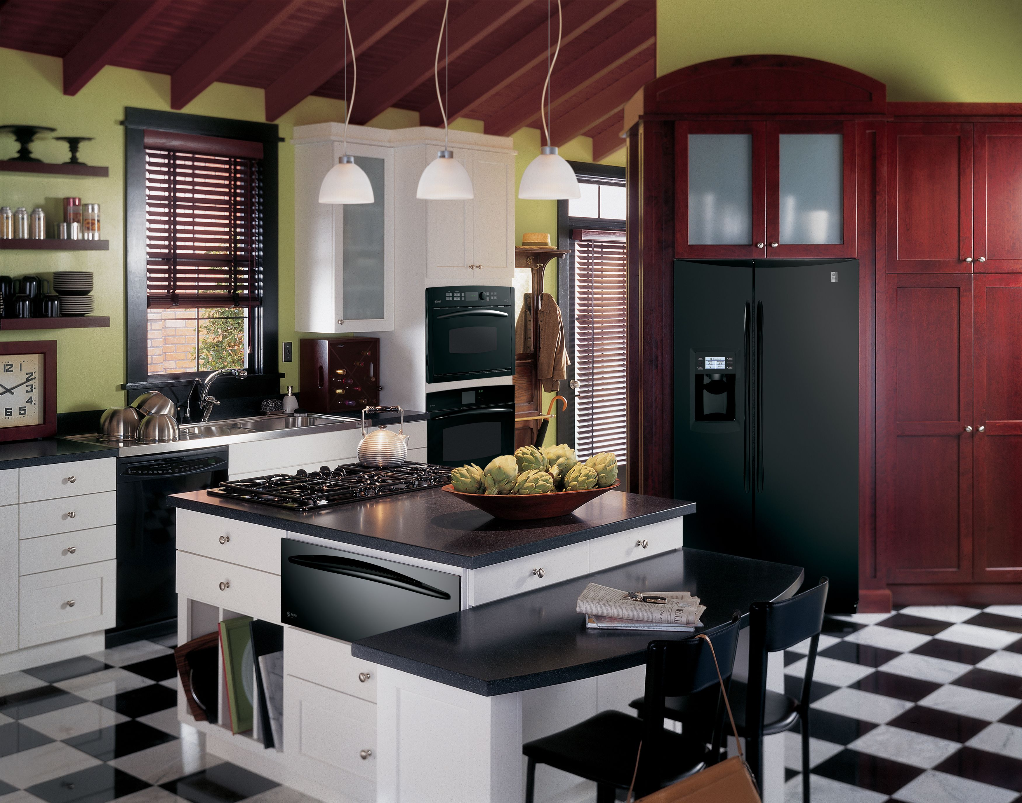 GE Profile kitchen with black appliances, green walls