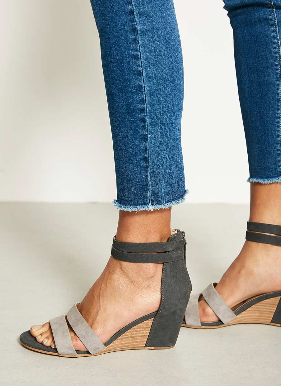 7825aab347e An alternative to a flat sandal are these low leather wedges. Featuring a  dark grey ankle strap with a back zip fastening