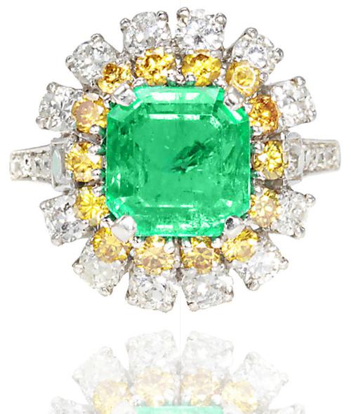 An emerald, colored diamond and diamond ring.