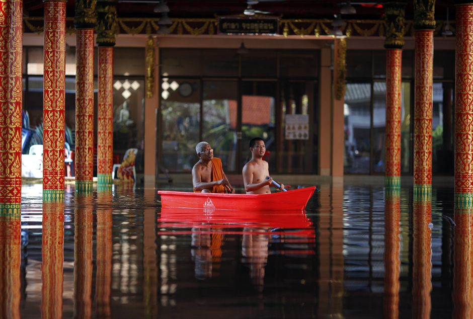 Buddhist monks paddle through a flooded temple where hundreds of victims found shelter in Bangkok.  1 Nov 2011, via Reuters