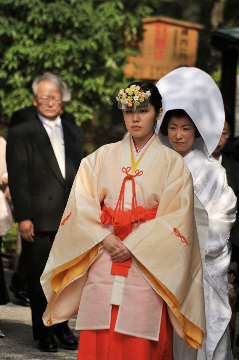 A Miko Dressed In Junihitoe Leading Members Of Wedding Party