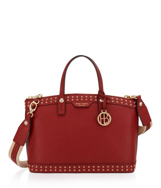 <p>The West 57th Grommet Satchel is red hot. This luxury handbag is crafted with fine Saffiano leather and adorned with edgy grommet detailing. Replete with all the inherent features of the beloved West 57th line, you'll continue to adore this designer satchel for its spacious satin interior with multiple pockets and the removable crossbody strap for varied wearable options.</p>