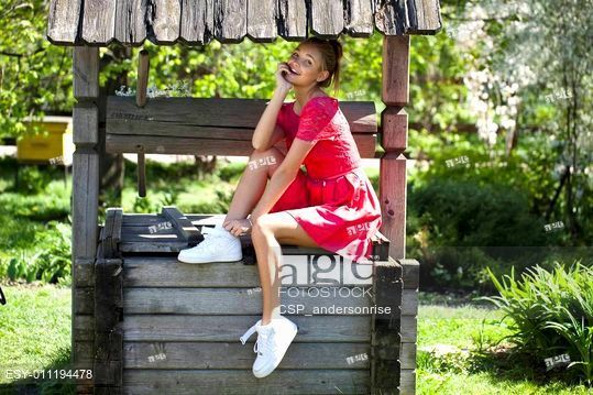 Beautiful girl sits on a wooden pit in the park