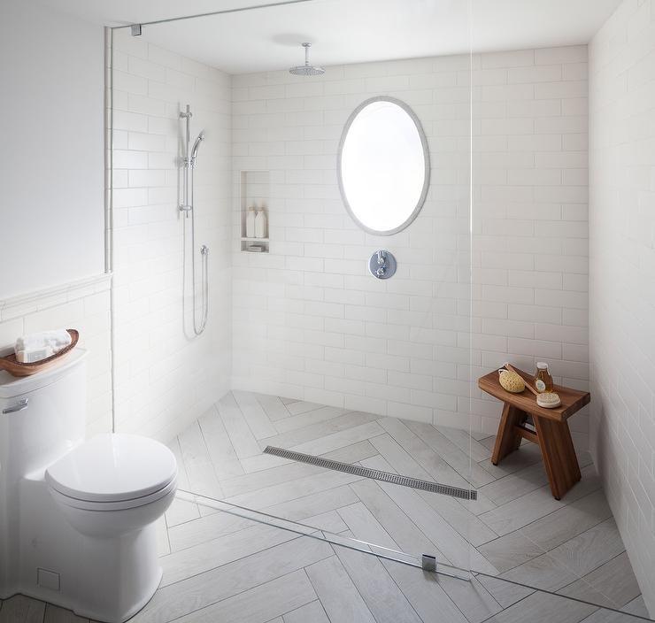 Gray Floor Level Shower Tiled With Gray Herringbone Pattern Tiles Featuring A Seamless Sliding Glass Guest Bathroom Design Shower Tile Creative Bathroom Design