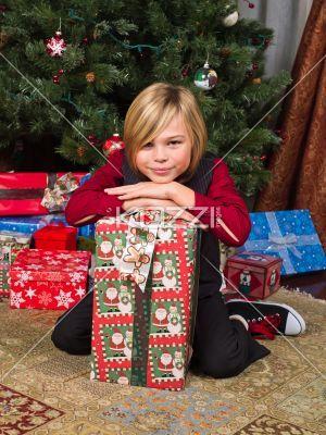 portrait of a boy sitting with his christmas tree. - Portrait of a cute boy sitting with his christmas tree, Model: Josh Chapman
