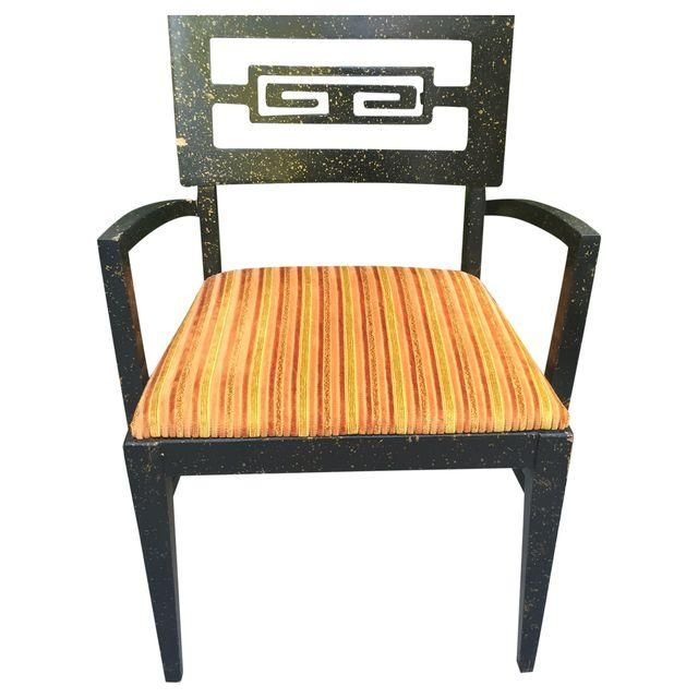 A unique, vintage chair that features an Art-Deco design in the back and an orange seat. It is very sturdy. There is a small chip on the chair back.