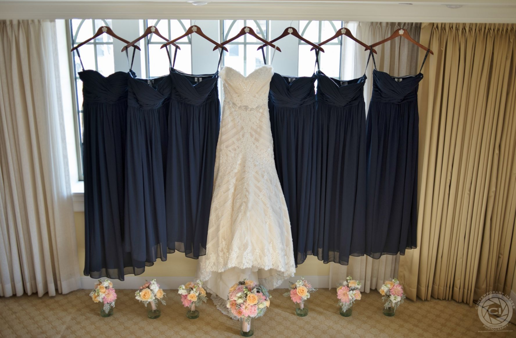 Navy blue chiffon bridesmaid dresses hanging next to wedding gown Loved the matching hangers for