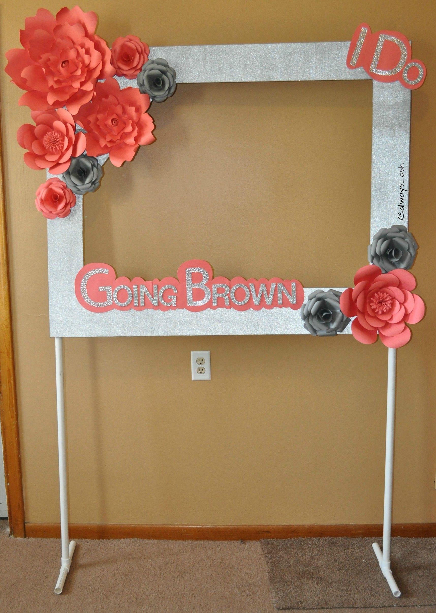 booth frame with paper flowers on a pvc pipe stand