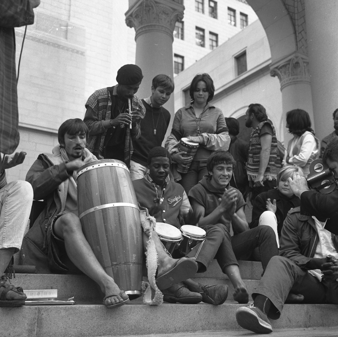 """""""Venice bohemians """" playing bongos on the steps of City Hall to protest city ordinance. Los Angeles, 1965."""