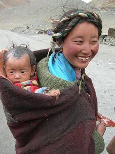Babywearing photo: Tibetan herder and baby. I want a shawl like that! :D I wish companies would sell coordinating shawls an as accessory.
