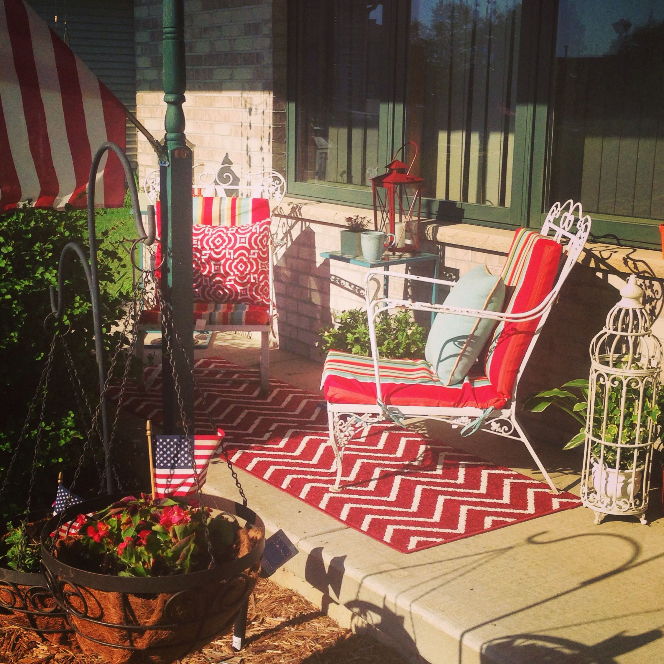 Small porch idea... French, bohemian, country... 2 vintage rod iron chairs, mixed with new and old, eclectic yet balanced tables, planters, and fabrics.  Cheery and comfortable...on a single mom budget!