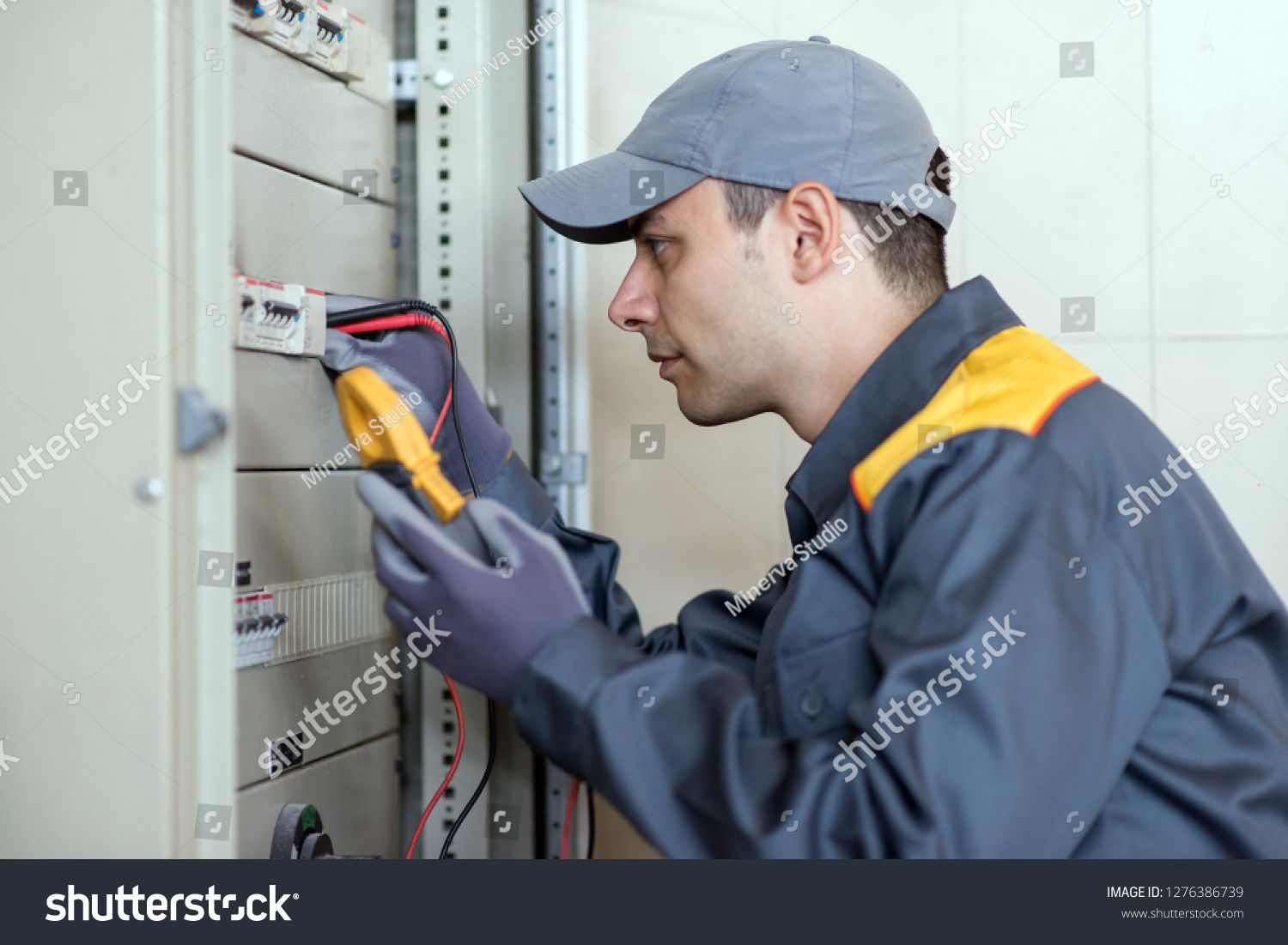 Electrician at work using a tester on an industrial panel