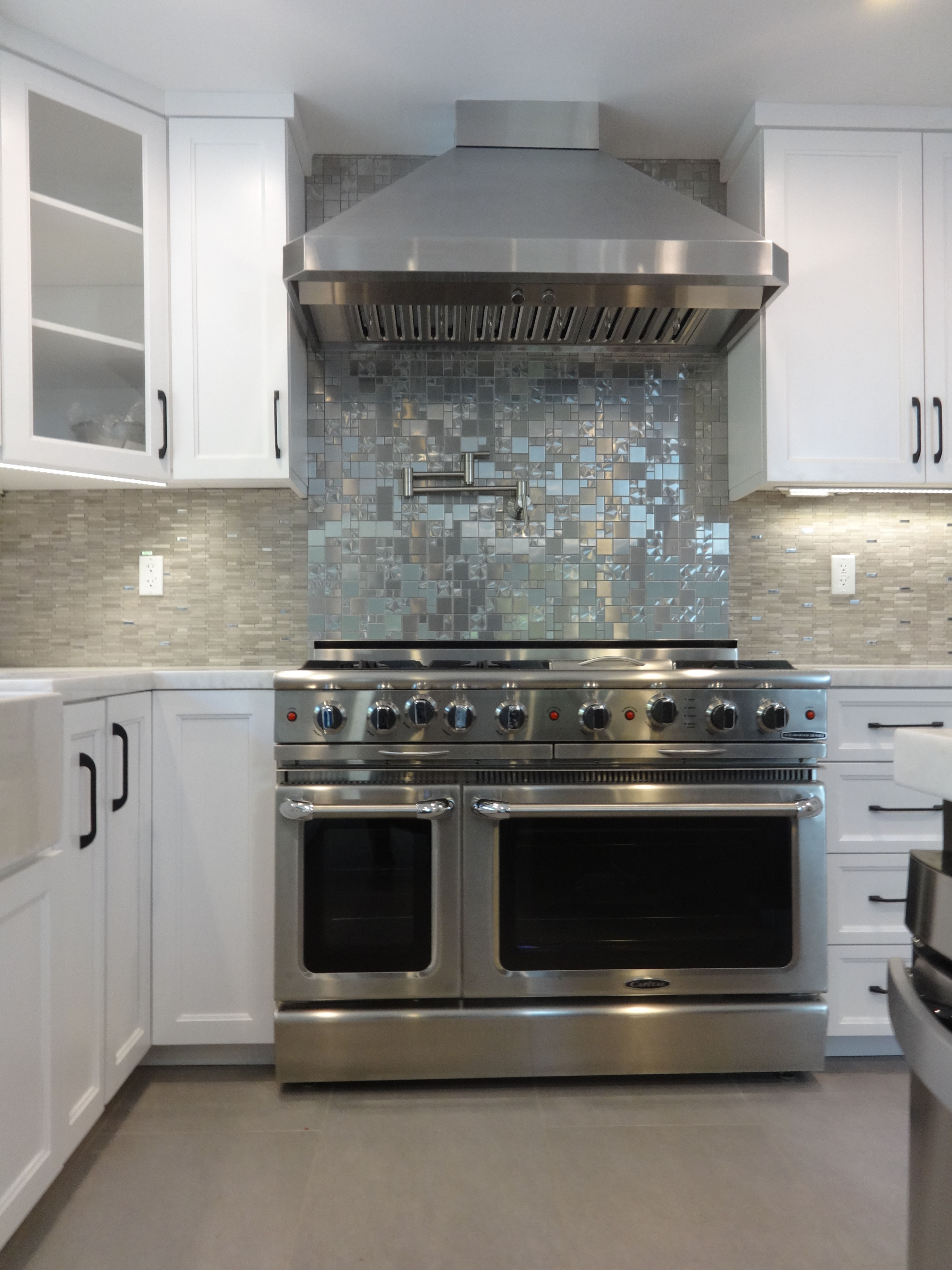 Beautiful white shaker with a stainless backsplash over the range #whiteshakercabinets