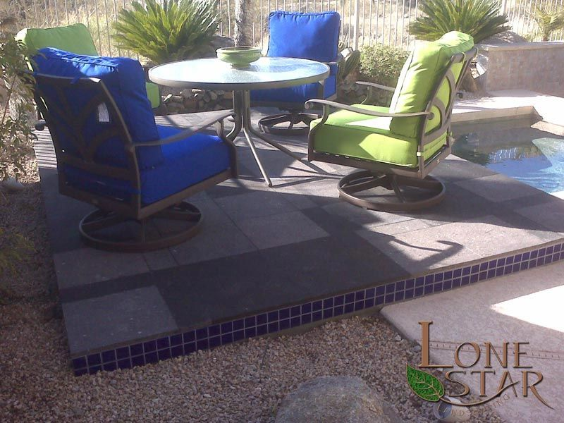 Black cantera tile on a raised area next to a pool and patio furniture set. - www.lonestaraz.com