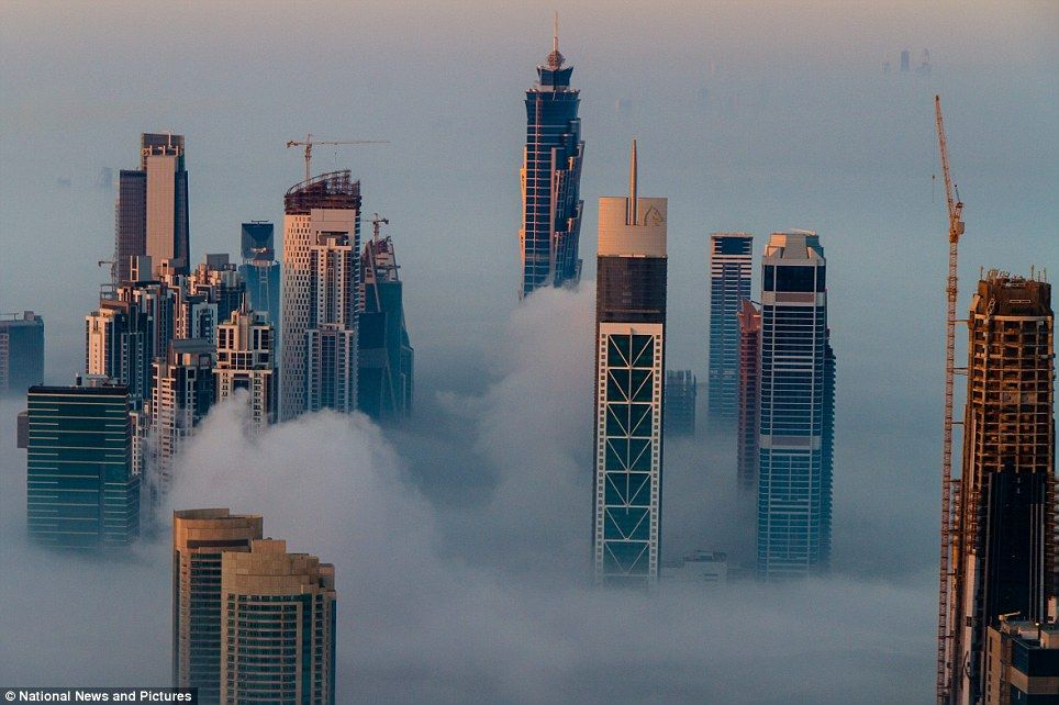 Rising above the mist: The world's tallest building pierces the atmosphere as Dubai's skyscrapers are shrouded by fog