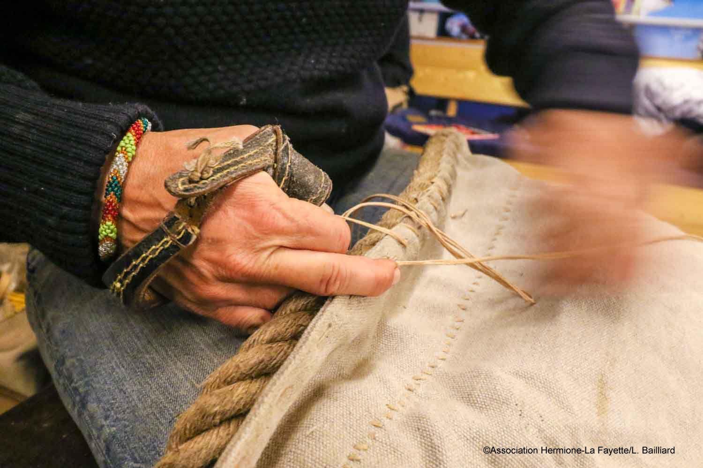 Il s'agit ici de l'installation de la ralingue, le cordage entourant la voile, qui va conférer à notre petit foc de rechange une grande partie de sa résistance et déterminer sa forme. En piquant d'une certaine façon, le ratio entre toile et cordage peut en effet être adapté afin de creuser la voile de la meilleure façon. Une réalisation qui demande de la technique, du doigté et de l'instinct.  Et si Anne est une fantastique prof, pleine de patience pour transmettre ses techniques, le doigté
