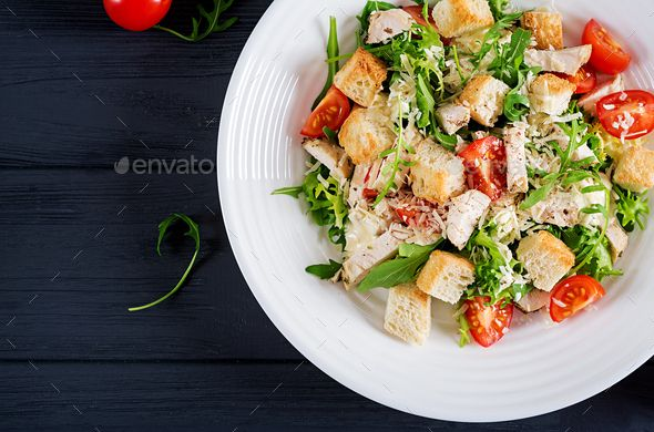 Healthy grilled chicken Caesar salad with tomatoes, cheese and croutons. by Timolina. Healthy grilled chicken Caesar salad with tomatoes, cheese and croutons. North American cuisine. Top view #AD #salad, #tomatoes, #cheese, #Caesar