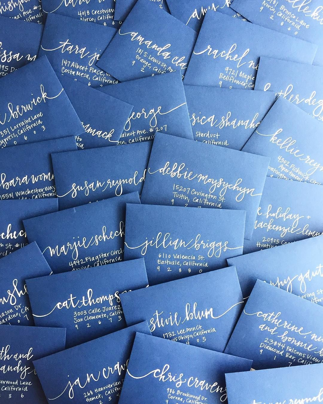 Navy and white invitation envelopes for a nautical baby shower. Calligraphy by Sea Calligraphy.