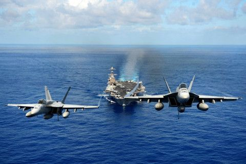 Two F-18 Super Hornets over the carrier USS John C. Stennis (CVN 74), somewhere in the Pacific, April 24.