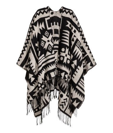698799356 Black/white patterned. Poncho in soft woven fabric with fringe at hem.  Length at…
