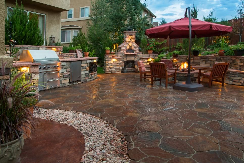 Any Type Of Gathering Will Be Perfect In This Cozy Backyard Oasis The Space Features An Outdoor Kitchen Stone Patio Design Patio Stones Outdoor Patio Designs