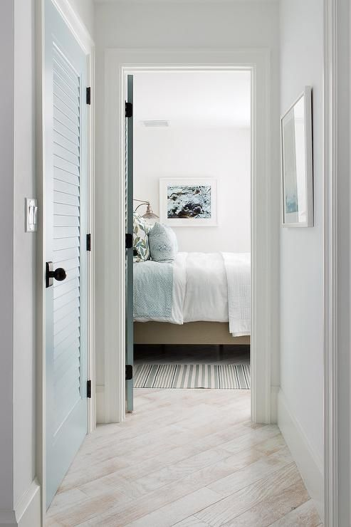 White Washed Wood Floors Lead Past A Blue Louvered Closet Door To A Bedroom Fitted With A White And Blue S Coastal Interiors Design Cottage Doors Interior Home
