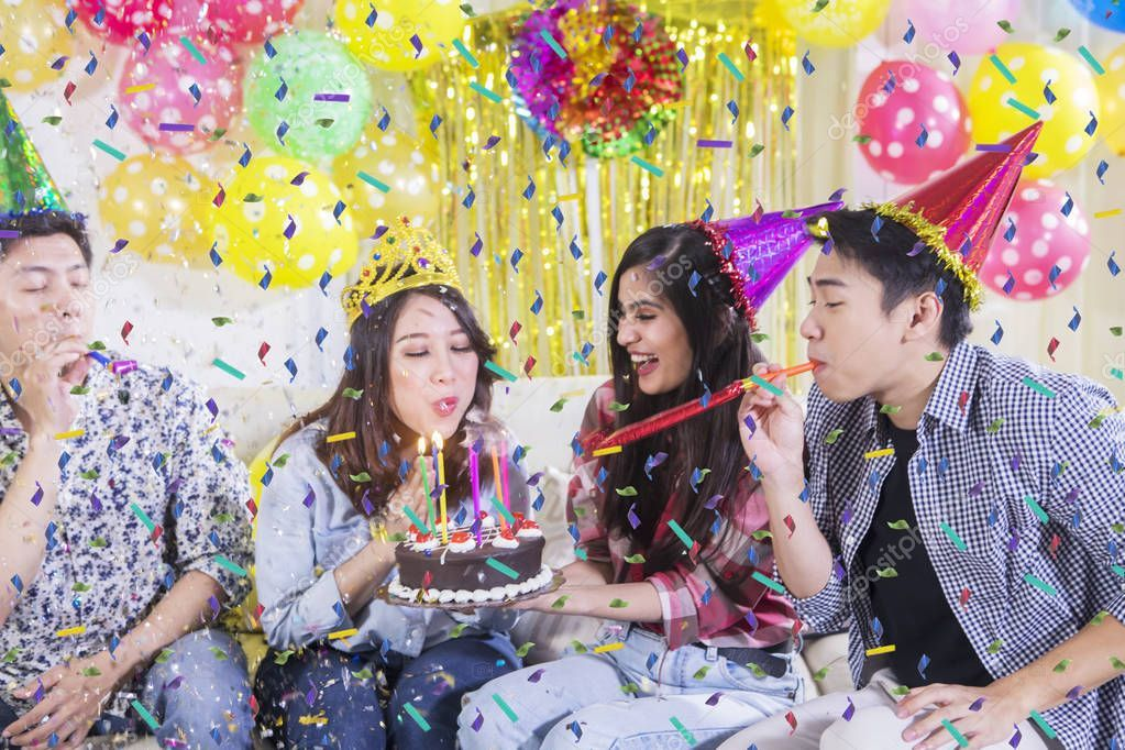 Young woman blowing candles with her friends  Stock Photo