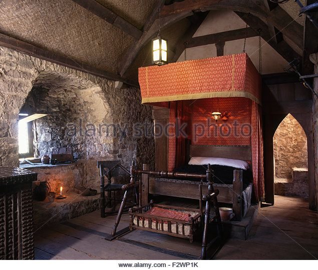 half tester bed in a medieval bedroom with an oak rocking cradle stock image
