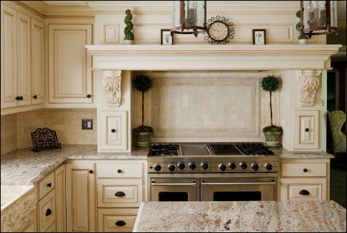 Cream Colored Custom Cabinetry And Range Hood With Corbels On Both Sides Of  The Stove
