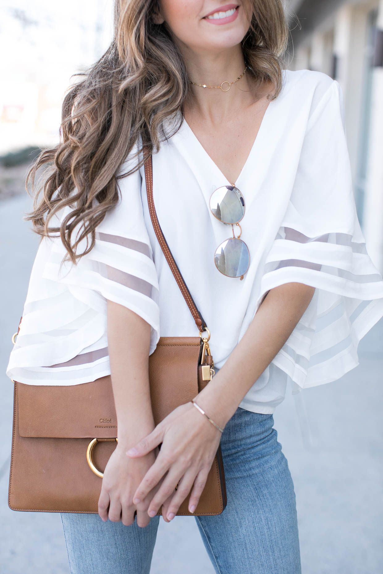 959cf0d3703659 spring outfit. white blouse. fun sleeves. big sleeves. jeans. bell sleeves.  sunglasses. satchel. cute outfit. style inspiration