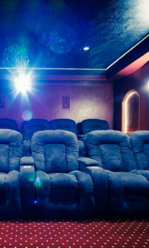 This home theater has seating for ten in super cushy microfiber navy recliners on two different tiers. The red and white polka-dot carpet matches the red walls.