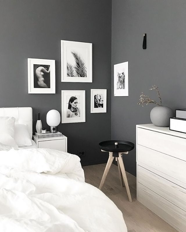 Stylish grey and white Nordic style bedroom.The predominantly white artwork  helps lighten up the stone grey walls.