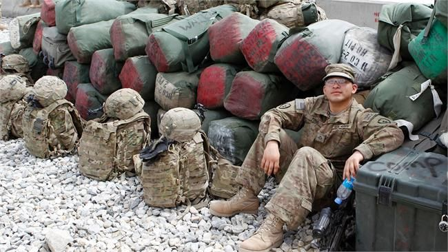 A U.S. army soldier rests among luggage while waiting for ...
