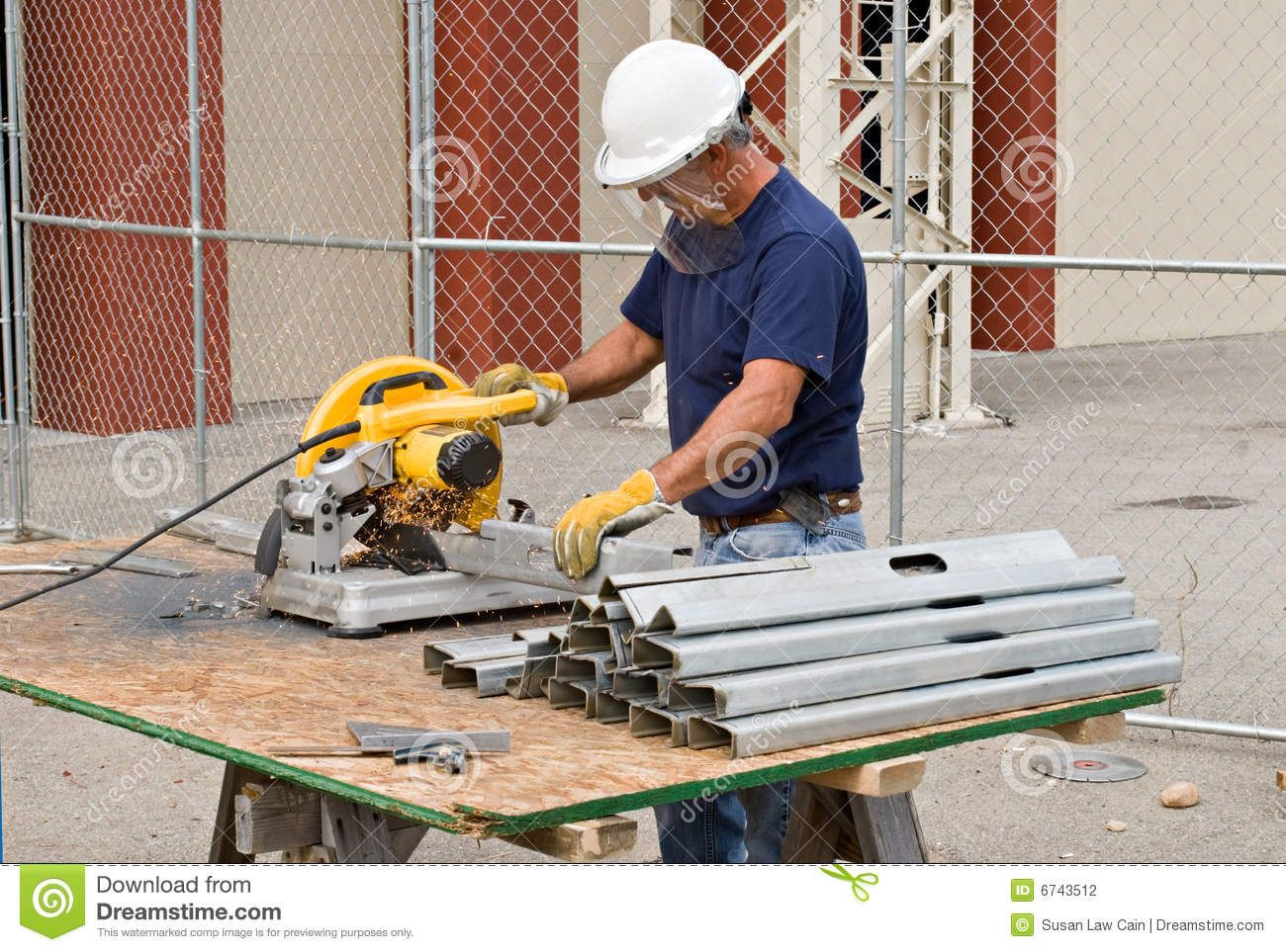 metal stud construction | Construction worker sawing pieces of metal ...