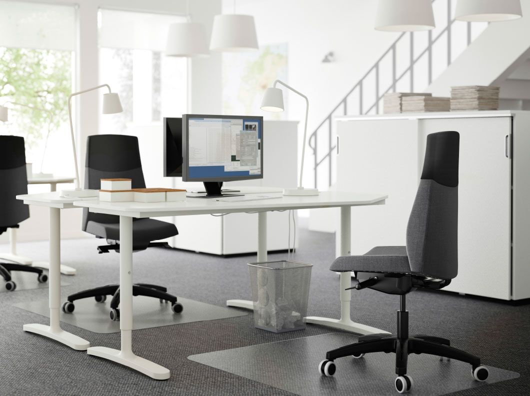 An open office with two white height adjustable desks in for Ufficio design ikea