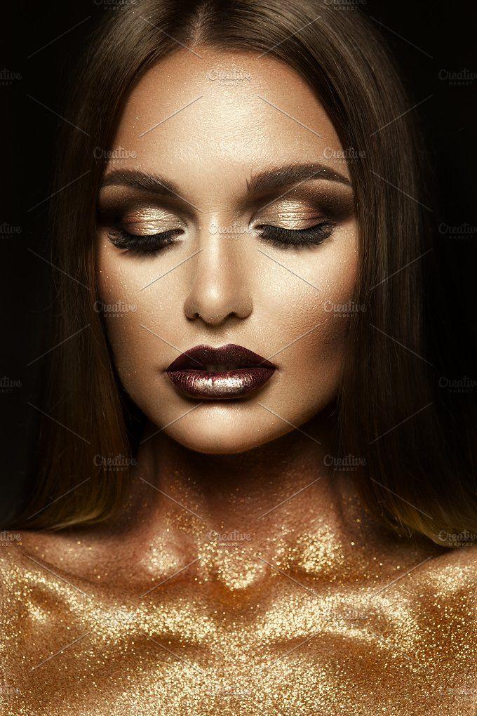 Beautyful girl with gold glitter on her face Glitter