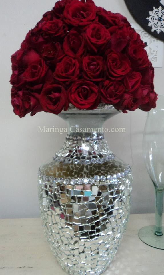 Arranjo de rosas vermelhas em vaso espelhado.