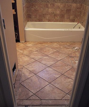 Attrayant Feel A Uniqueness In Every Step Of Bathroom Floor Tile Designs: The Lovely  Bathtub In A White And Clean Condition Combines With A Brown Diagonal Floor  ...
