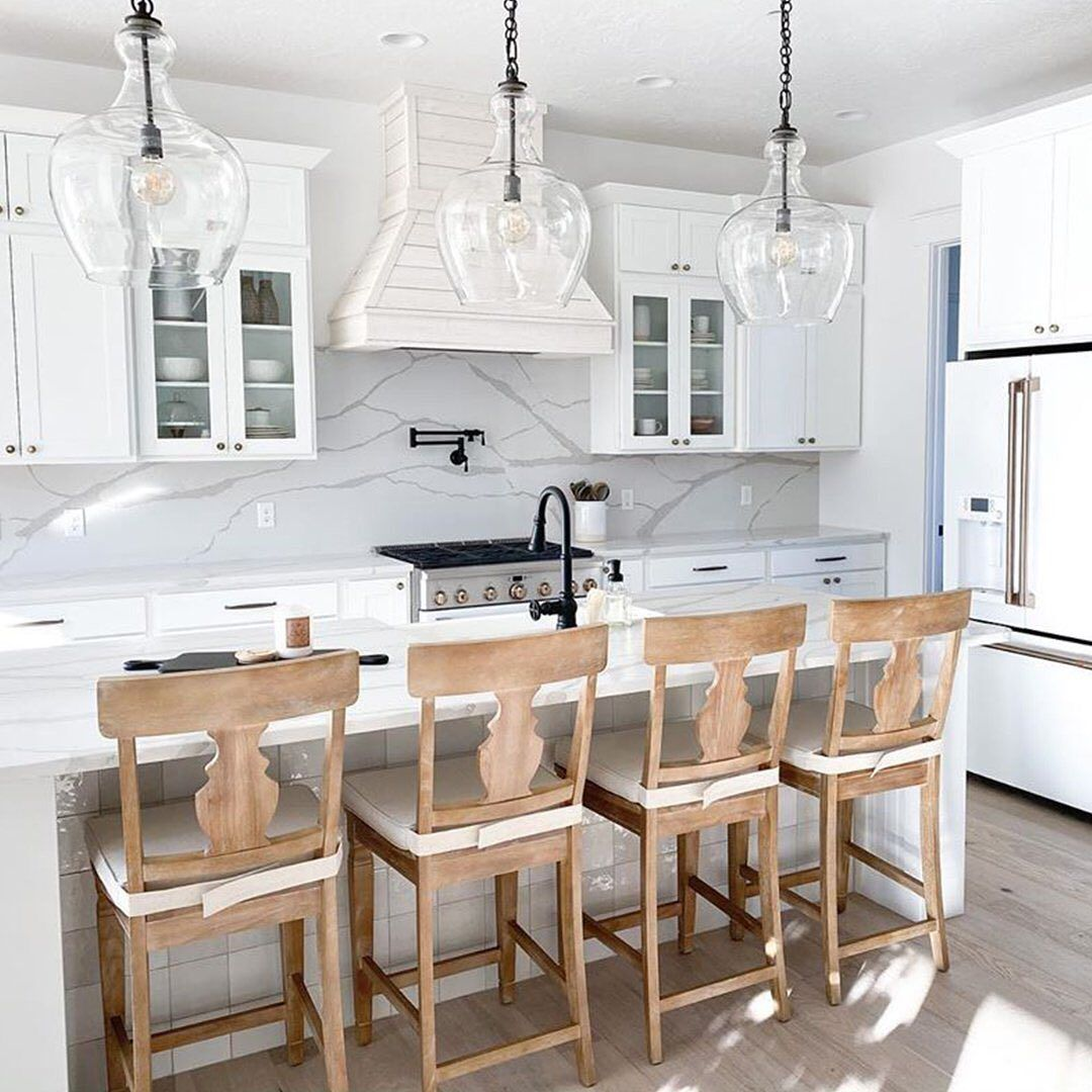 All-white interiors are everywhere right now. We love how @our_sweet_haven warms this trend with farmhouse-style wooden counter stools! #pier1love • • • #farmhousestyle #modernfarmhouse #farmhousedesign #whitekitchen #neutraldecor #kitchendecor #counterstools