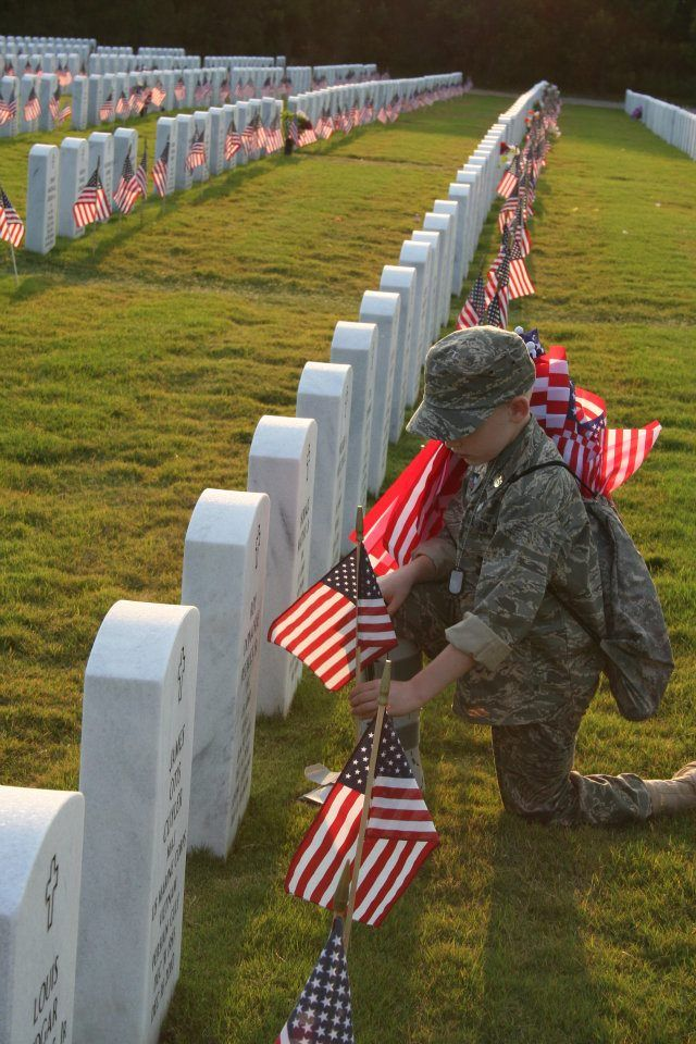 Young boy placing flags at the Georgia National Cemetery.