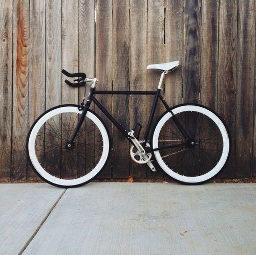 black fixie bike white saddle wooden backdrop