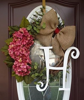 Grapevine wreath with monogram, flowers and a burlap bow.